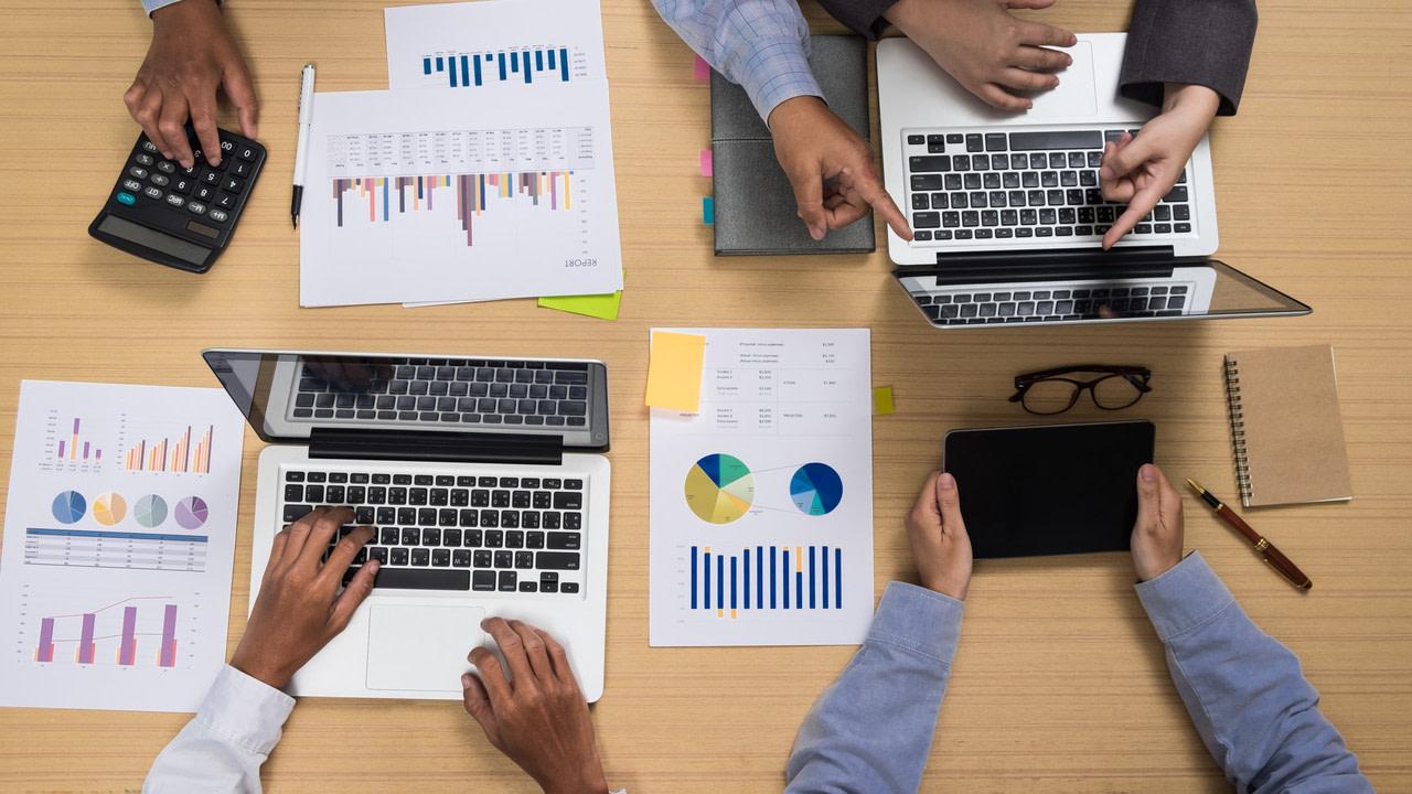 Profissionais mostram habilidades dos pré-vendedores em uma mesa de trabalho com computadores e gráficos.