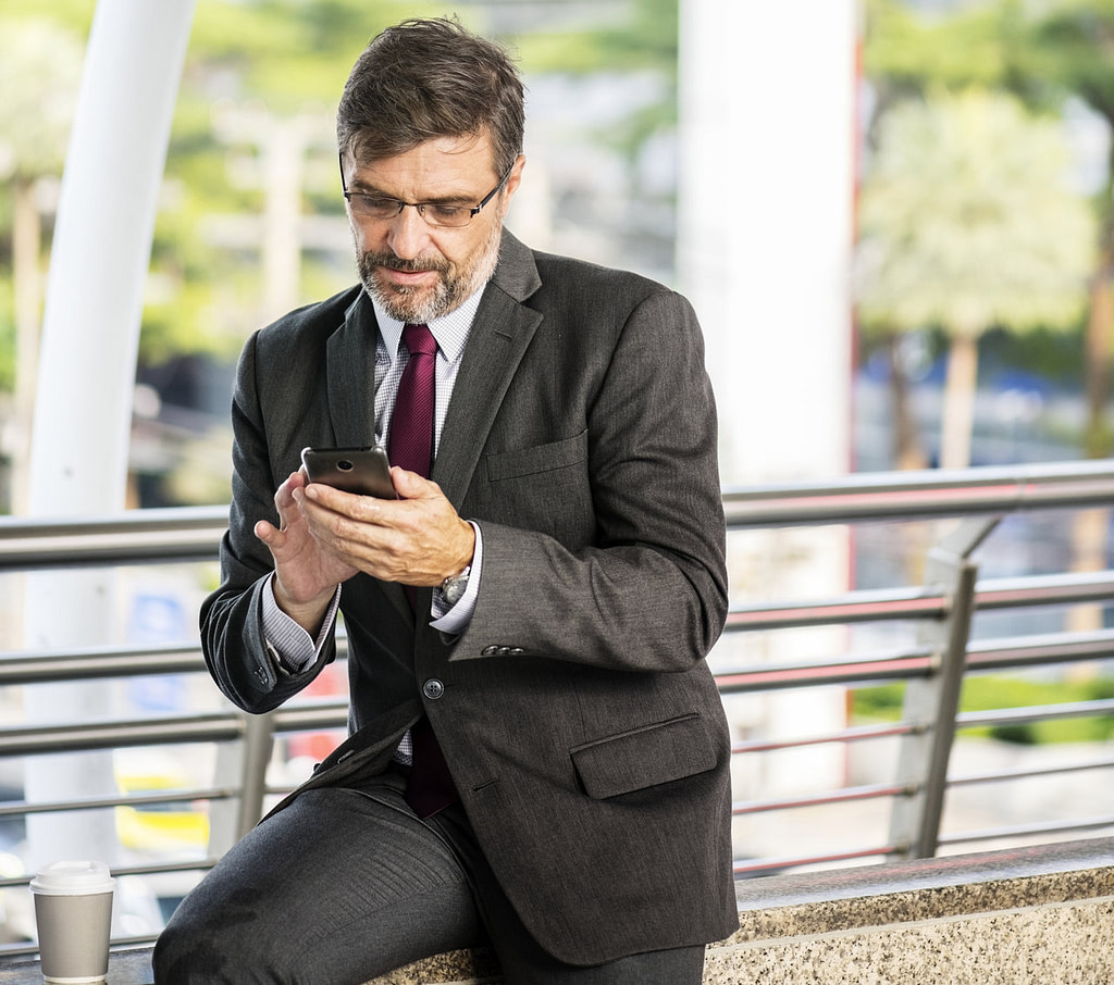Homem interagindo com celular representa boas práticas de redes sociais para corretores.
