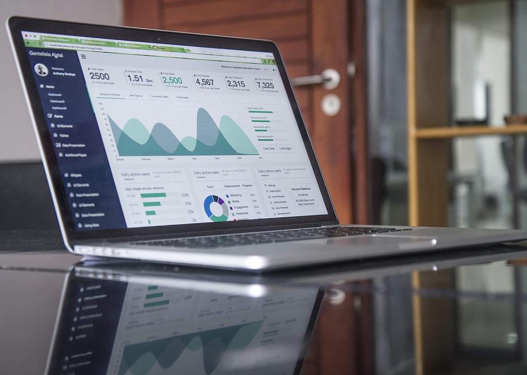 Computador com gráficos ilustra gestão data driven para imobiliárias.