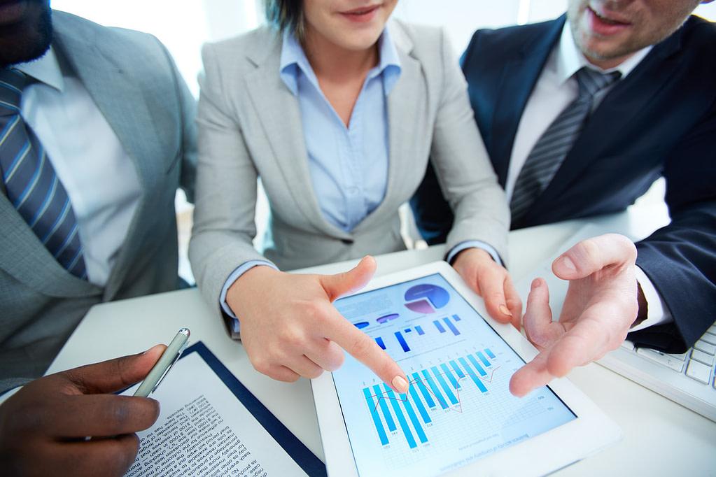 Equipe analisa indicadores de marketing e vendas para sua imobiliária.